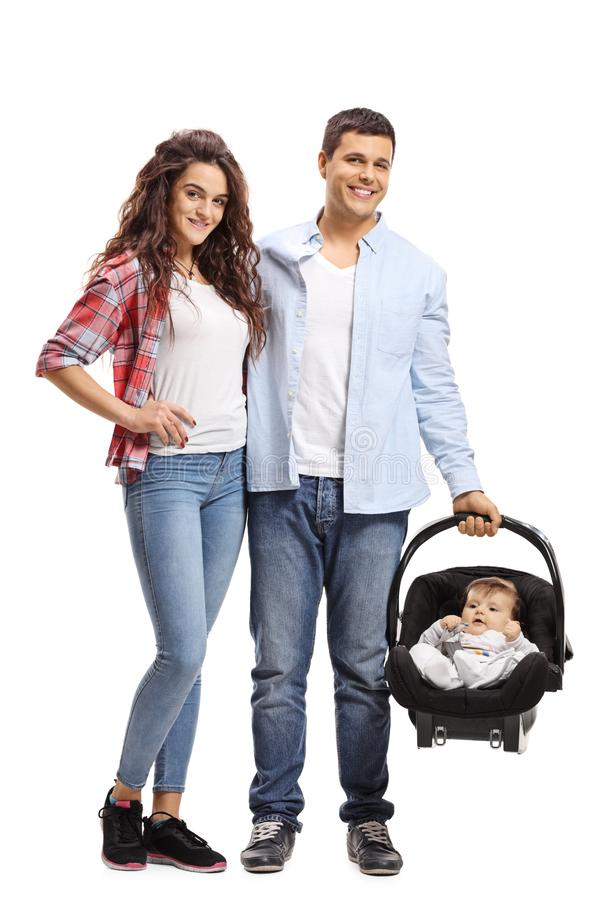 Família nova de uma mãe, do pai e de um bebê em um banco de carro infantil fotos de stock