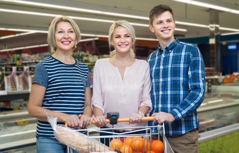Família nova e uma mulher idosa que faz a compra em um supermarke fotos de stock