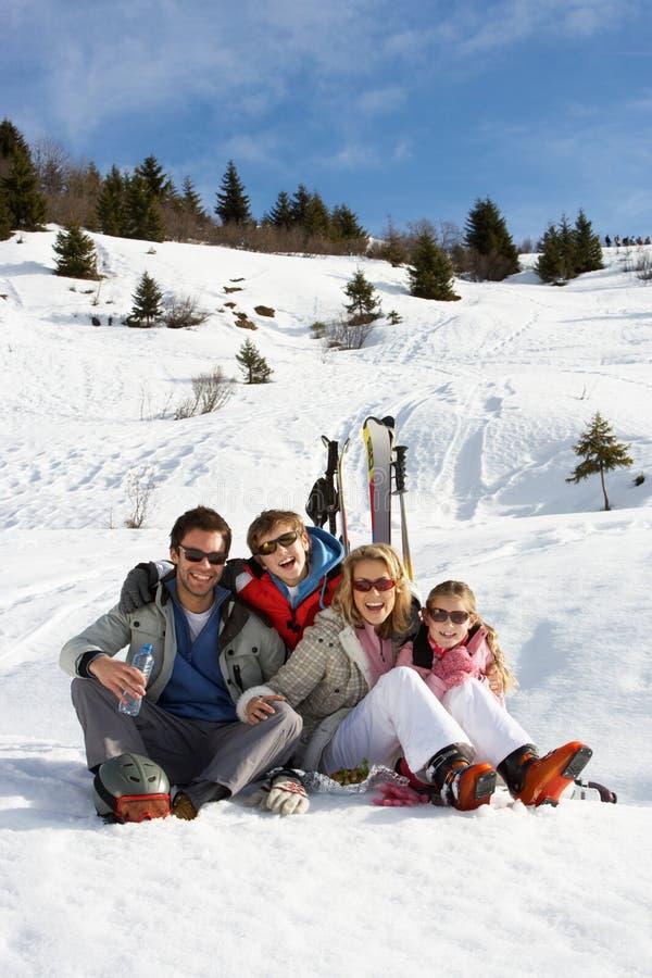 Família nova em férias do esqui imagens de stock