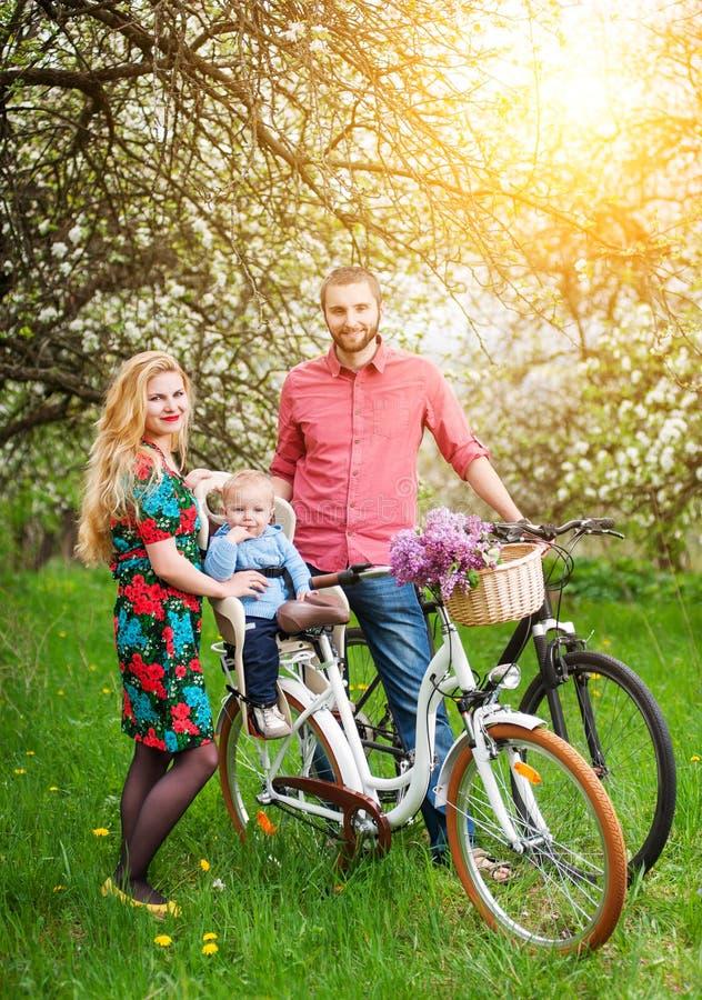 Família nova em um jardim das bicicletas na primavera foto de stock royalty free