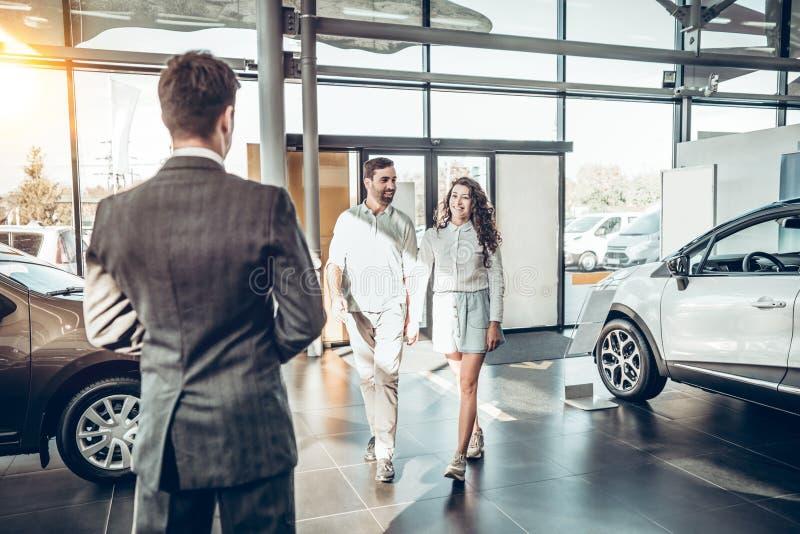 A família nova entra o concessionário automóvel para escolher o carro comprá-lo foto de stock