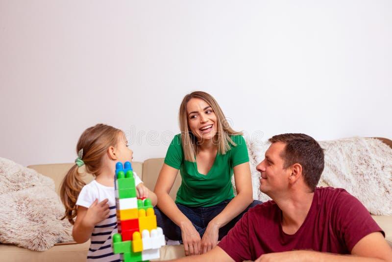 A família nova está tendo o divertimento que joga com filha bonito em casa fotografia de stock royalty free