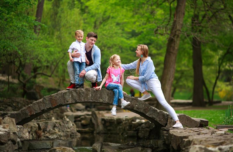 Fam?lia nova feliz com as crian?as no parque verde do ver?o na ponte de pedra sobre o rio na floresta fotografia de stock royalty free