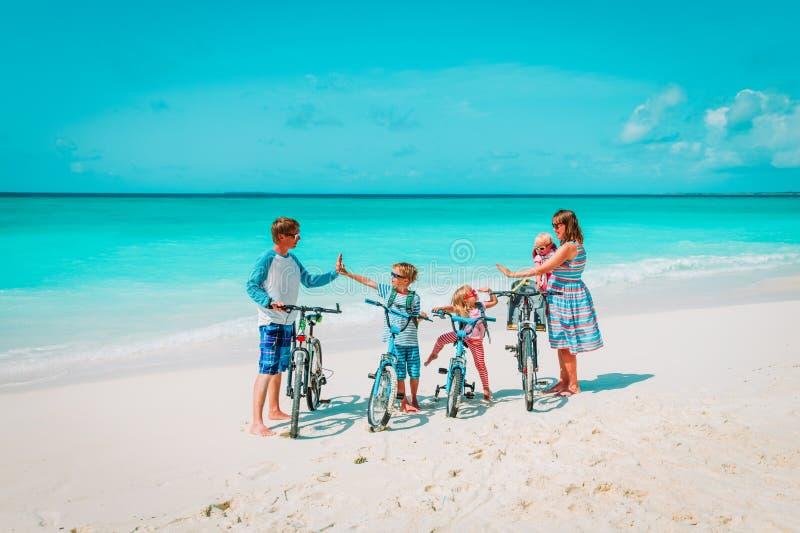 Família nova feliz com as crianças que montam bicicletas na praia foto de stock