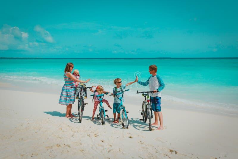 Família nova feliz com as crianças que montam bicicletas na praia imagem de stock
