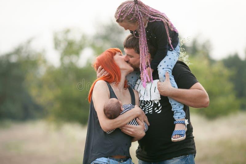 Família nova feliz com as duas crianças na caminhada no parque Parents a AR imagem de stock royalty free