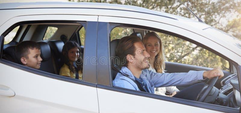 Família nova feliz com as duas crianças que conduzem em seu carro foto de stock royalty free