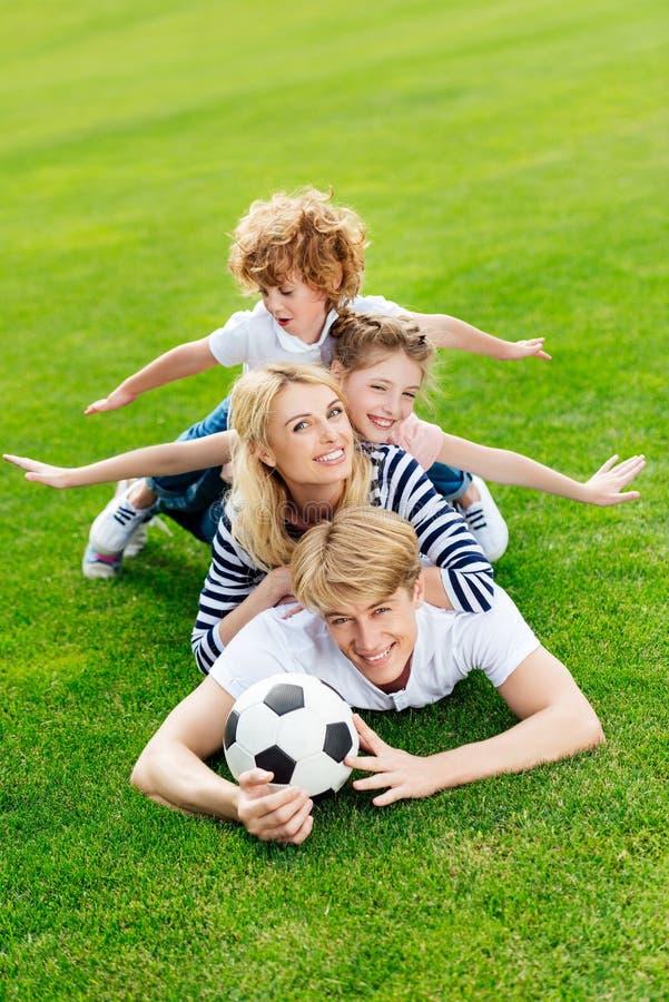 família nova feliz com a bola de futebol que encontra-se no gramado verde imagens de stock