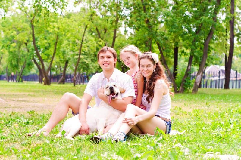 Família nova feliz com Labrador imagens de stock