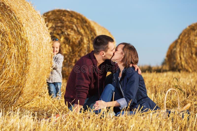 Família nova feliz com a menina bienal ao lado dos pacotes de feno no campo fotos de stock royalty free