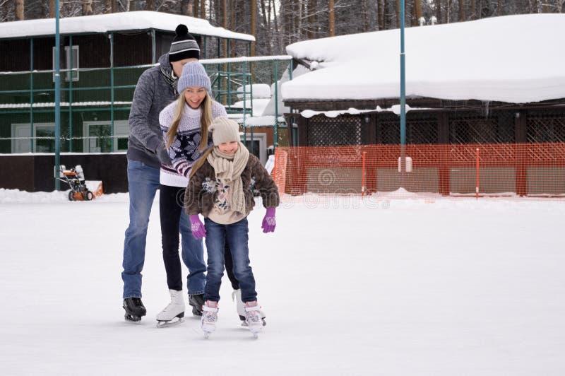 Família nova feliz com o patim da criança na pista de gelo exterior no inverno Família bonita que anda e que joga no gelo dentro imagens de stock