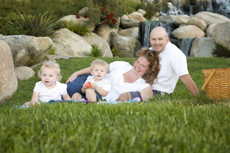 Família nova feliz com o retrato dos gêmeos no parque imagens de stock