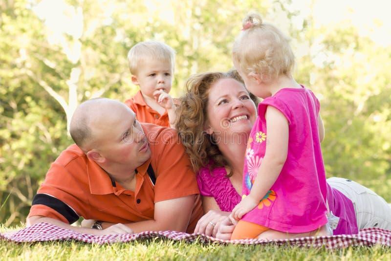 Família nova feliz com os gêmeos bonitos no parque foto de stock royalty free