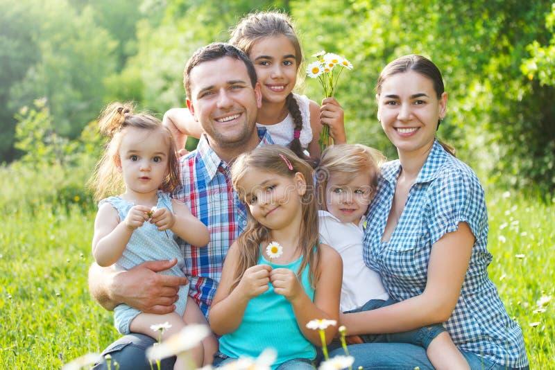 Família nova feliz com quatro crianças fora fotografia de stock royalty free