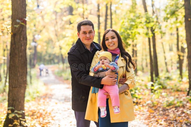 Família nova feliz com sua filha que passa o tempo exterior no parque do outono imagens de stock royalty free