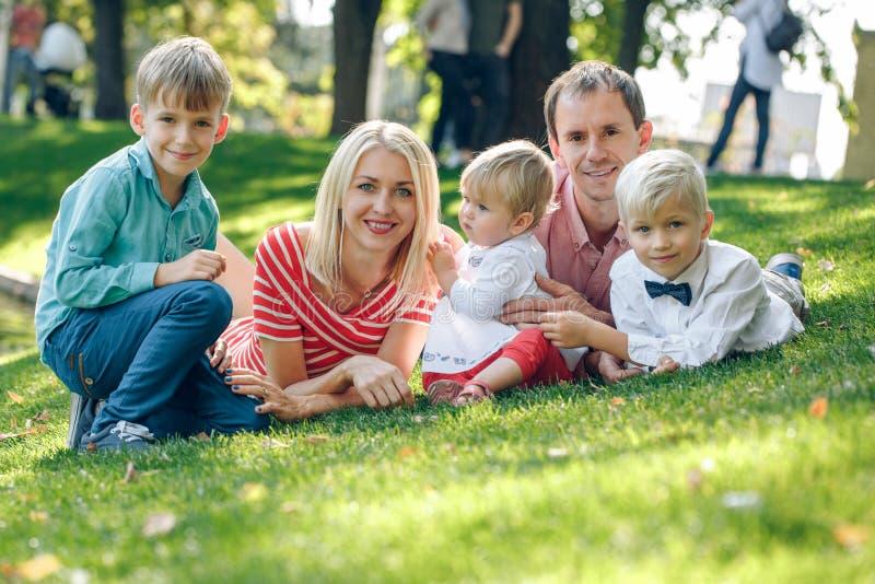 Família nova feliz com três crianças fora fotos de stock royalty free