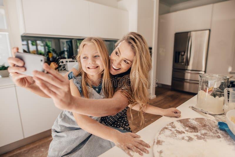 Família nova feliz de tomar o selfie na cozinha fotos de stock