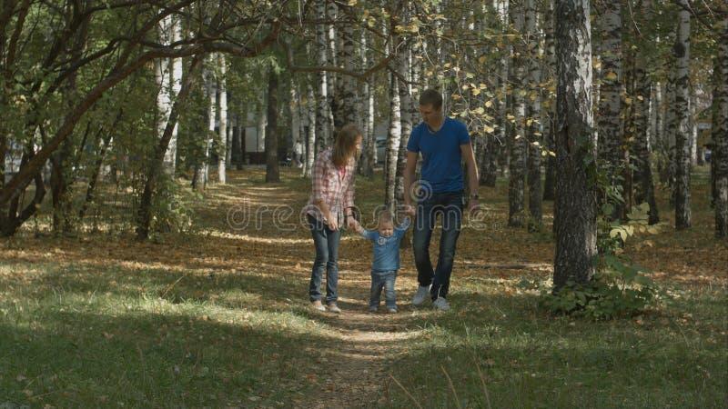 A família nova feliz está tendo o divertimento no parque do outono fora em um dia ensolarado Mãe, balanço do pai seu bebê pequeno fotografia de stock royalty free