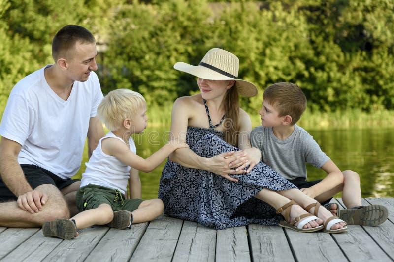 A família nova feliz, a mãe do pai e dois filhos pequenos estão sentando-se no cais do rio fotos de stock royalty free