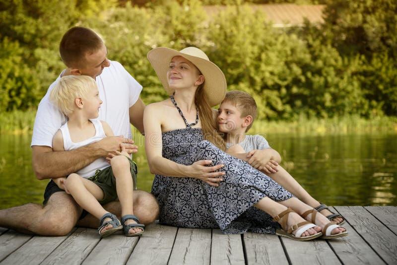 A família nova feliz, a mãe do pai e dois filhos pequenos estão sentando-se no cais do rio foto de stock