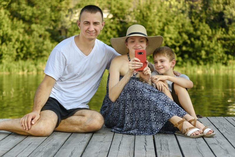 A família nova feliz, a mãe do pai e dois filhos pequenos são de assento e de tomada selfies no cais do rio imagens de stock