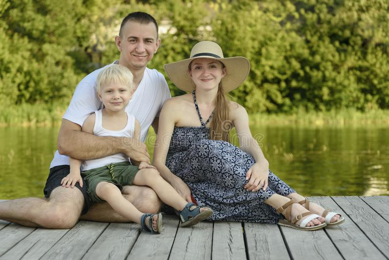 A família nova feliz, a mãe do pai e pouco filho louro estão sentando-se no cais do rio imagem de stock royalty free