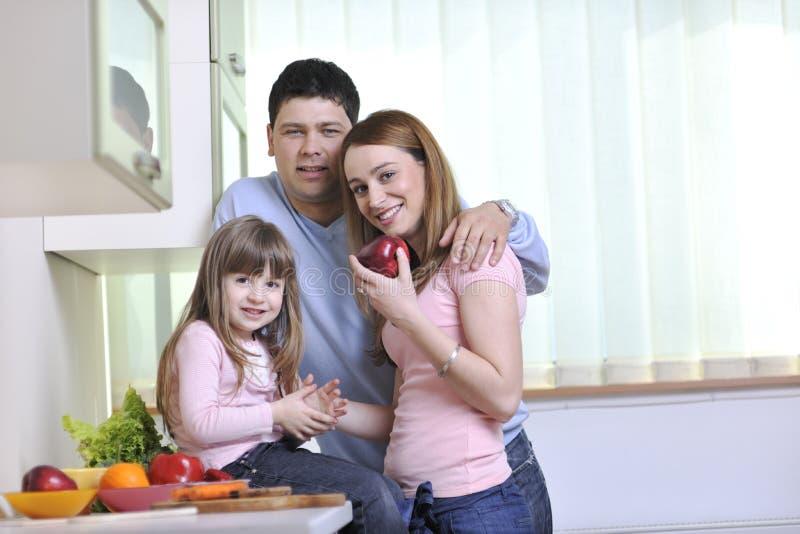 Família nova feliz na cozinha imagem de stock royalty free