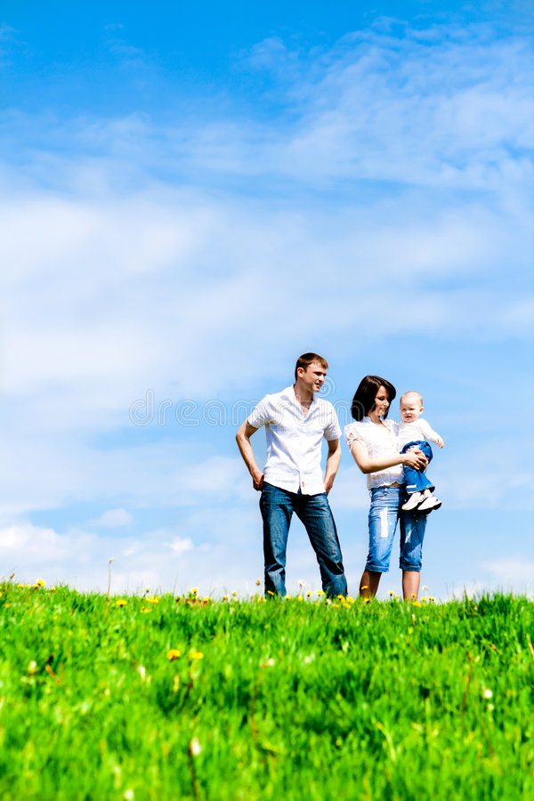 Família nova feliz na grama verde sobre o céu foto de stock