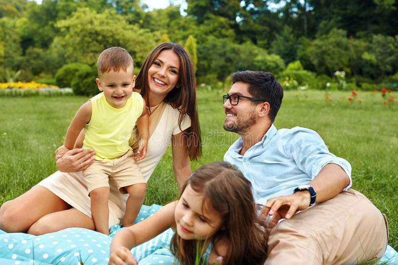 Família nova feliz no parque Pais e crianças que têm o divertimento, jogando foto de stock