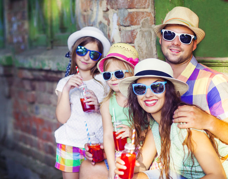 Família nova feliz nos chapéus e nos óculos de sol vestindo da rua imagem de stock royalty free