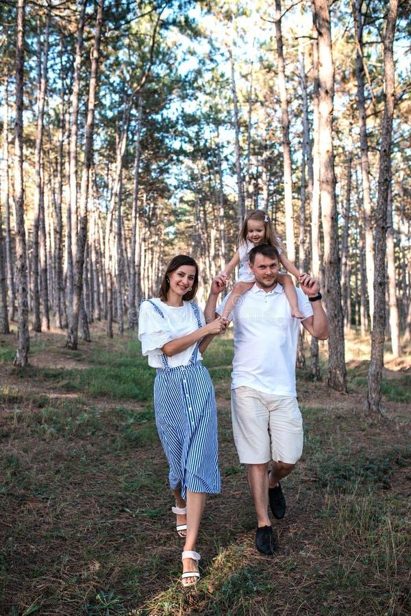 Família nova feliz que anda na floresta imagem de stock