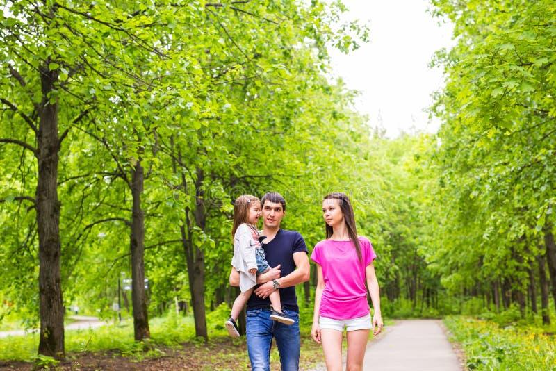 Família nova feliz que anda na natureza verde imagem de stock