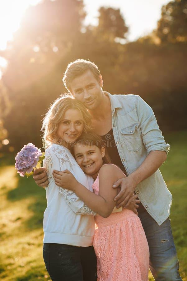 Família nova feliz que aprecia um dia ensolarado junto fora foto de stock royalty free