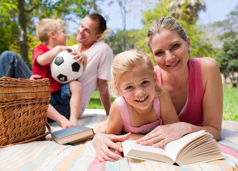 Família nova feliz que aprecia um piquenique imagens de stock royalty free