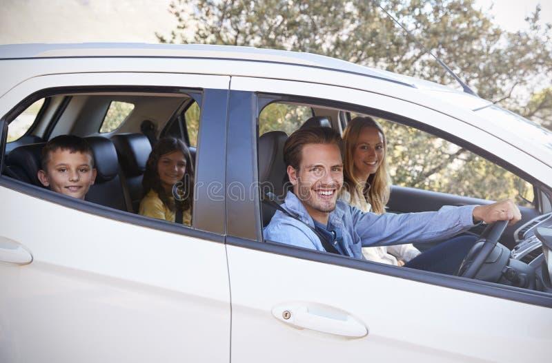 Família nova feliz que conduz em seu carro que olha à câmera fotografia de stock