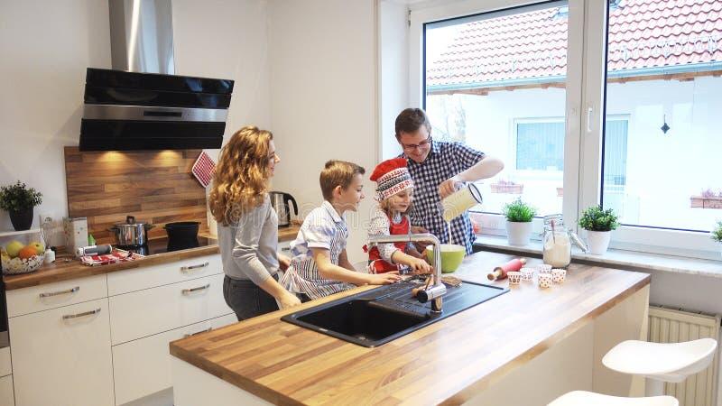 Família nova feliz que cozinha e que tem o divertimento na manhã no kitc fotos de stock