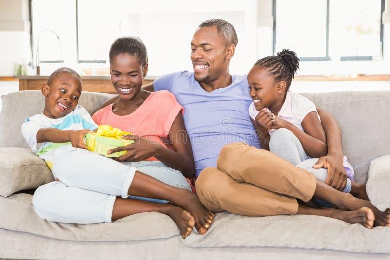 Família nova feliz que dá um presente a seu filho foto de stock