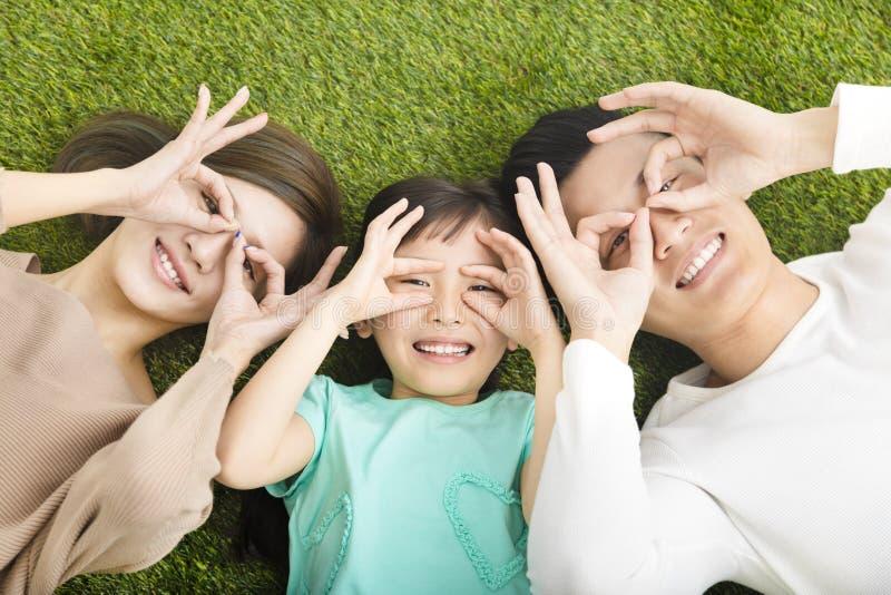 Família nova feliz que encontra-se na grama fotos de stock royalty free