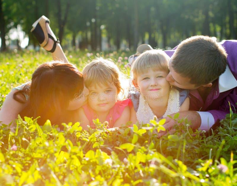 Família nova feliz que encontra-se na grama imagem de stock