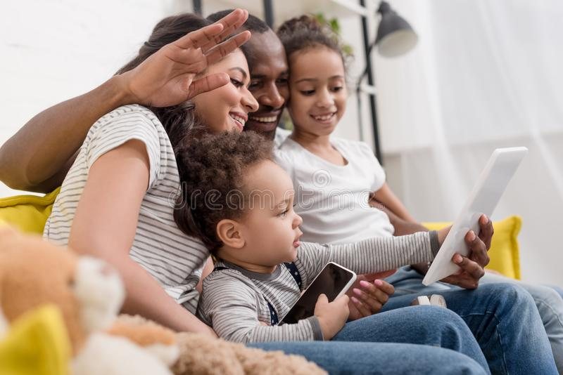 família nova feliz que faz a chamada video com tabuleta imagem de stock