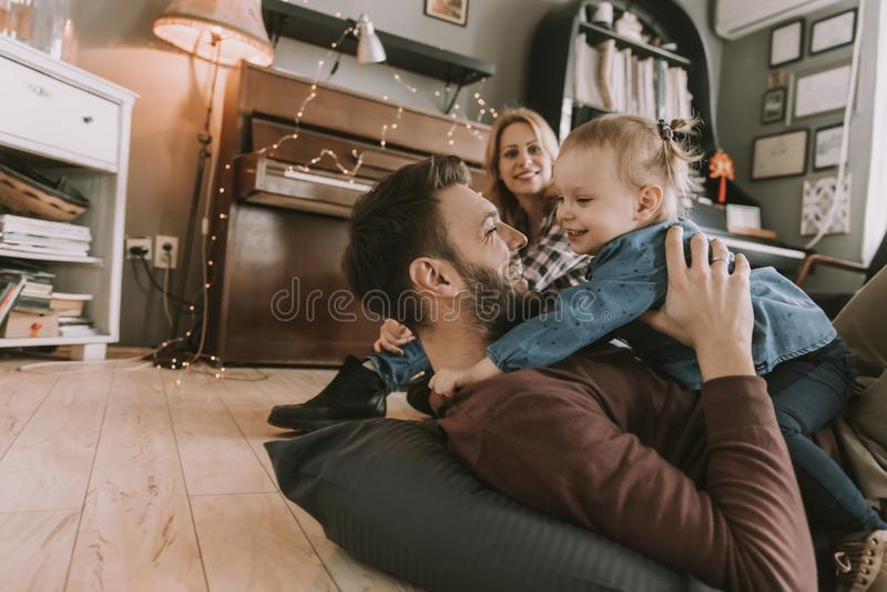 Família nova feliz que joga no assoalho imagem de stock