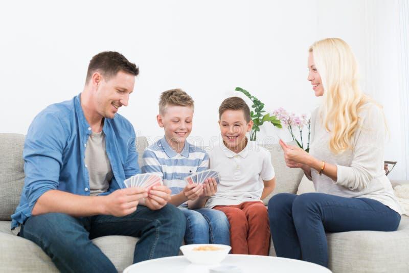 Família nova feliz que joga o jogo de cartas em casa foto de stock