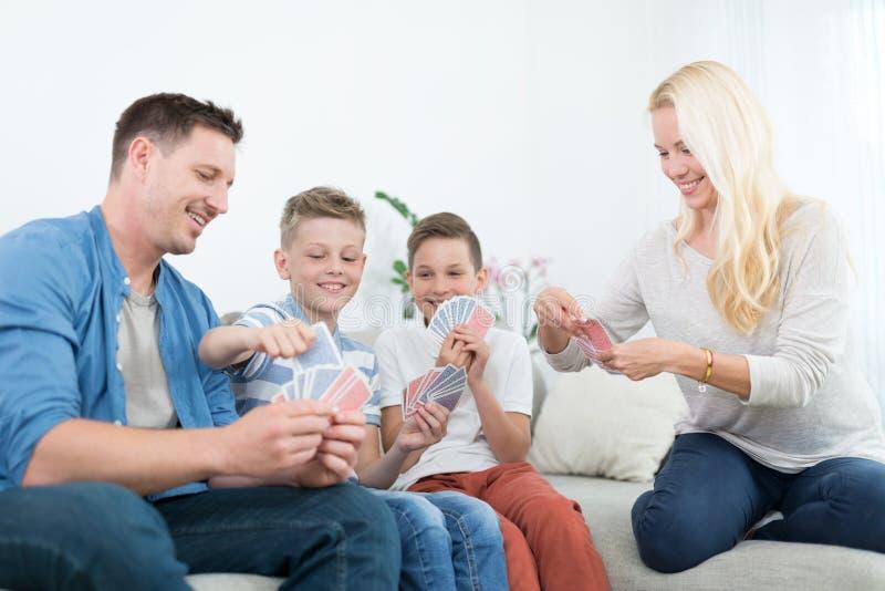 Família nova feliz que joga o jogo de cartas em casa foto de stock royalty free