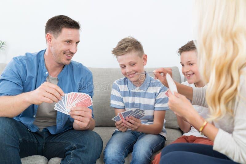 Família nova feliz que joga o jogo de cartas em casa fotos de stock royalty free