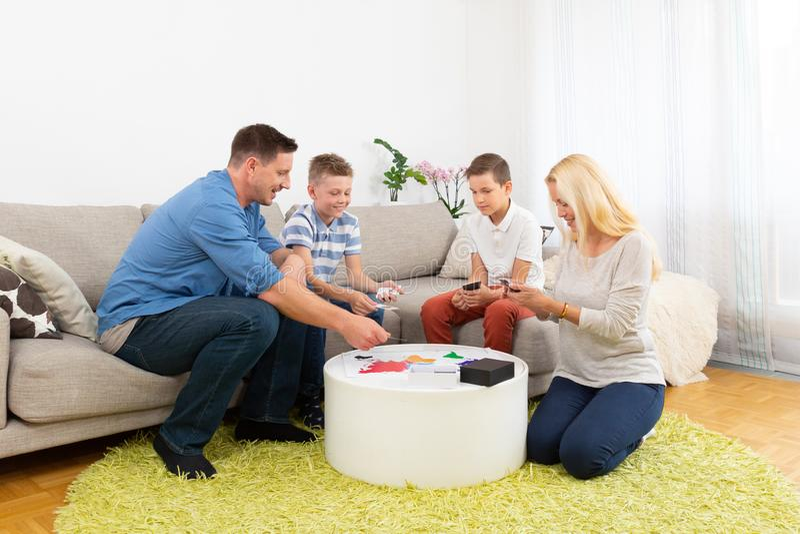 Família nova feliz que joga o jogo de cartas em casa imagens de stock royalty free