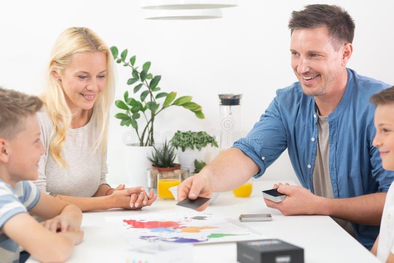 Família nova feliz que joga o jogo de cartas na mesa de jantar na casa moderna brilhante imagem de stock royalty free
