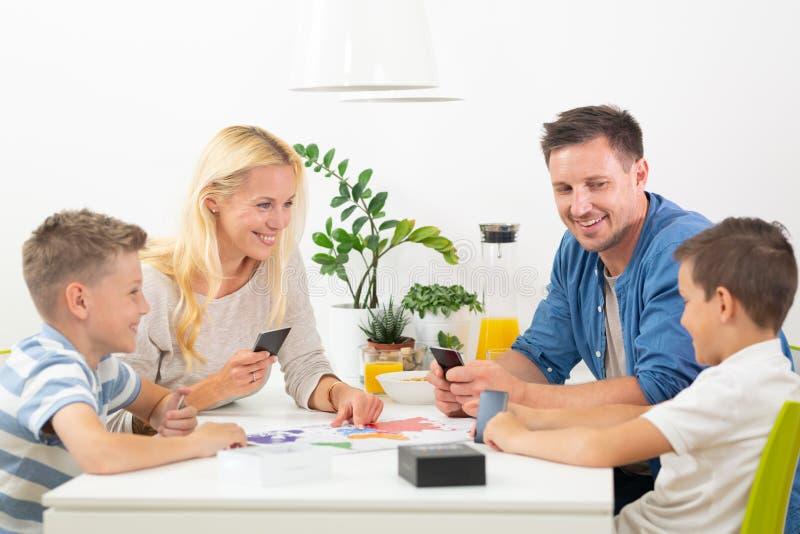 Família nova feliz que joga o jogo de cartas na mesa de jantar na casa moderna brilhante imagem de stock