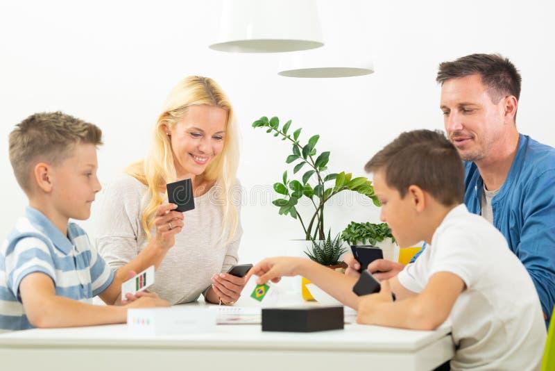 Família nova feliz que joga o jogo de cartas na mesa de jantar na casa moderna brilhante imagens de stock