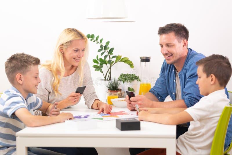 Família nova feliz que joga o jogo de cartas na mesa de jantar na casa moderna brilhante fotografia de stock