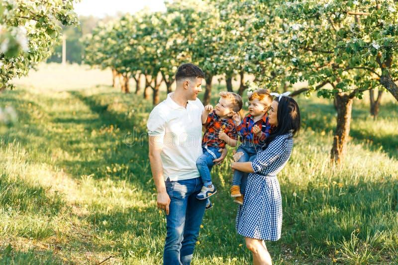 Família nova feliz que passa o tempo junto fora na natureza verde Pais que jogam com gêmeos Walkng da família de quatro pessoas imagem de stock royalty free
